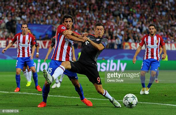 Robert Lewandowski of Bayern Muenchen battles for the ball with Stefan Savic of Atletico Madrid during the UEFA Champions League group D match...