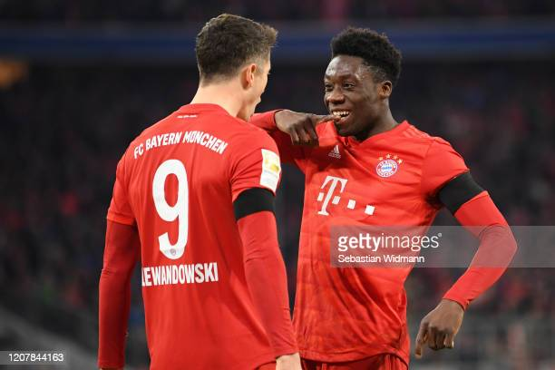 Robert Lewandowski of Bayern Muenchen celebrates after scoring his team's third goal with teammate Alphonso Davies during the Bundesliga match...