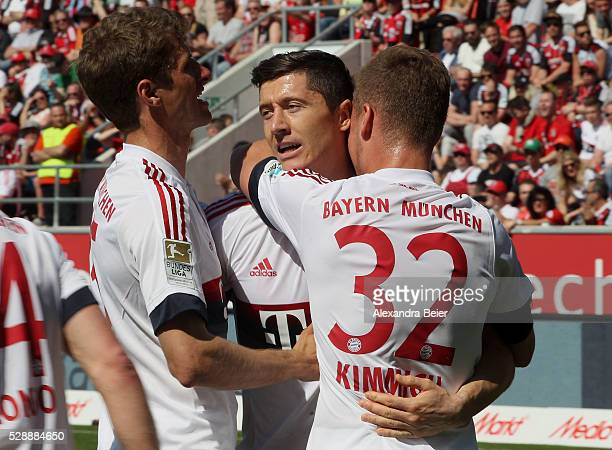 Robert Lewandowski of Bayern Muenchen celebrates his penalty goal with teammates Thomas Mueller and Joshua Kimmich during the Bundesliga match...