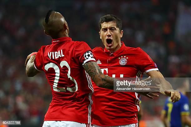 Robert Lewandowski of Bayern Muenchen celebrates scoring his sides first goal with Arturo Vidal of Bayern Muenchen during the UEFA Champions League...