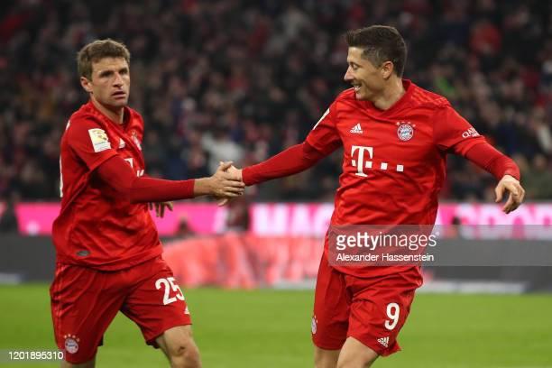 Robert Lewandowski of Bayern Muenchen celebrates scoring the opening goal with his team mate Thomas Mueller during the Bundesliga match between FC...