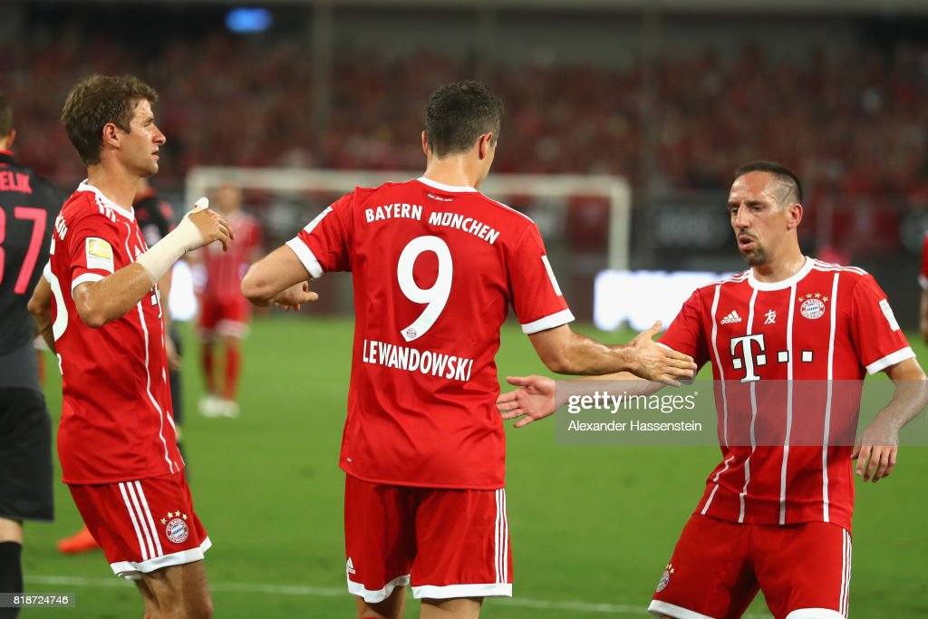 Robert Lewandowski of Bayern Muenchen celebrates scoring the opening goal with his team mates Thomas Mueller (L) and Franck Ribery during the Audi Football Summit 2017 match between Bayern Muenchen and Arsenal FC at Shanghai Stadium during the Audi Summer Tour 2017 on July 19, 2017 in Shanghai, China.