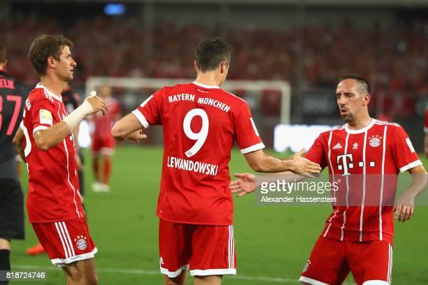 Robert Lewandowski of Bayern Muenchen celebrates scoring the opening goal with his team mates Thomas Mueller and Franck Ribery during the Audi...