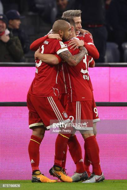 Robert Lewandowski of Bayern Muenchen celebrates with Arturo Vidal of Bayern Muenchen and Joshua Kimmich of Bayern Muenchen after he scored his teams...