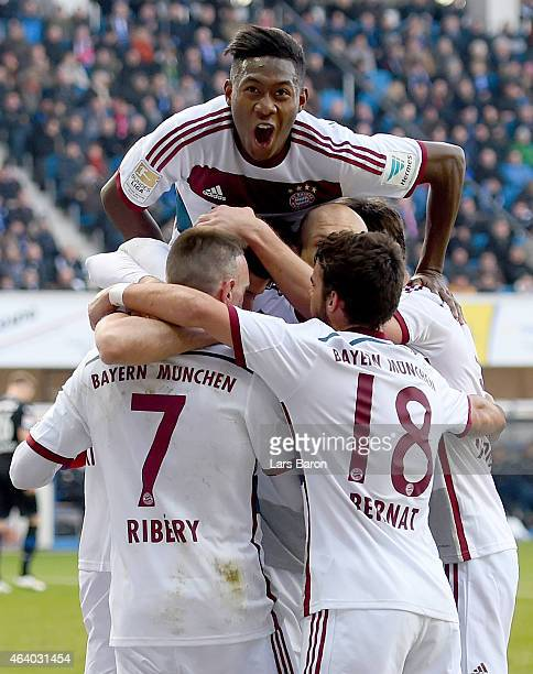 Robert Lewandowski of Bayern Muenchen celebrates with David Alaba and other team mates after scoring his teams first goal during the Bundesliga match...