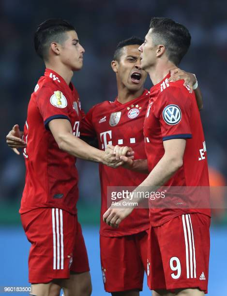 Robert Lewandowski of Bayern Muenchen celebrates with James Rodriguez of Bayern Muenchen and Thiago Alcantara of Bayern Muenchen after he scored a...