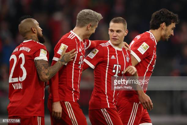Robert Lewandowski of Bayern Muenchen celebrates with Joshua Kimmich of Bayern Muenchen and his team after he scored his teams third goal to make it...