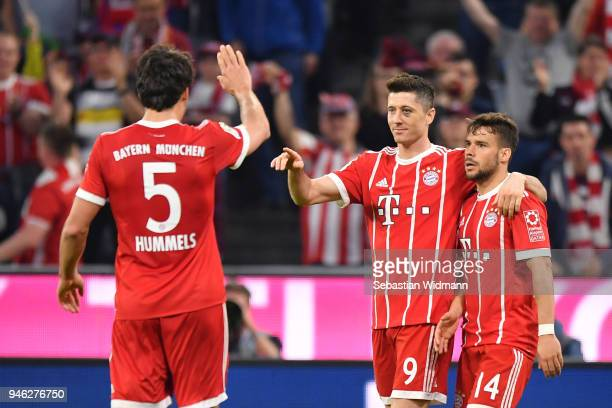 Robert Lewandowski of Bayern Muenchen celebrates with Juan Bernat and Mats Hummels of Bayern Muenchen after he scored his teams fifth goal during the...