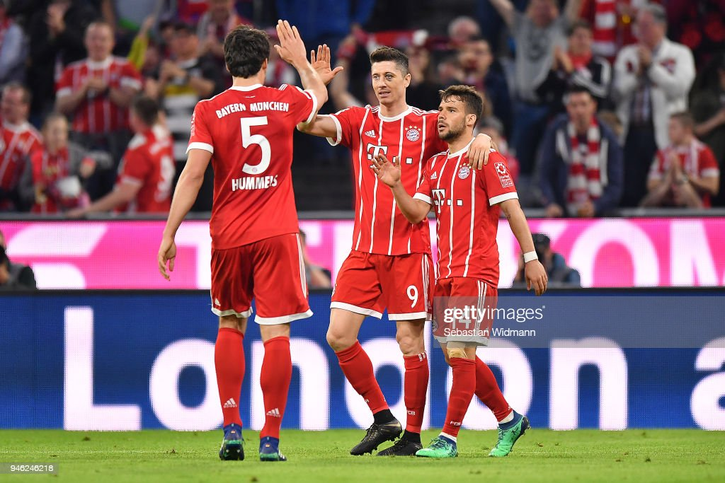Robert Lewandowski of Bayern Muenchen celebrates with Juan Bernat of Bayern Muenchen (r) and Mats Hummels of Bayern Muenchen after he scored a goal to make it 5:1 during the Bundesliga match between FC Bayern Muenchen and Borussia Moenchengladbach at Allianz Arena on April 14, 2018 in Munich, Germany.