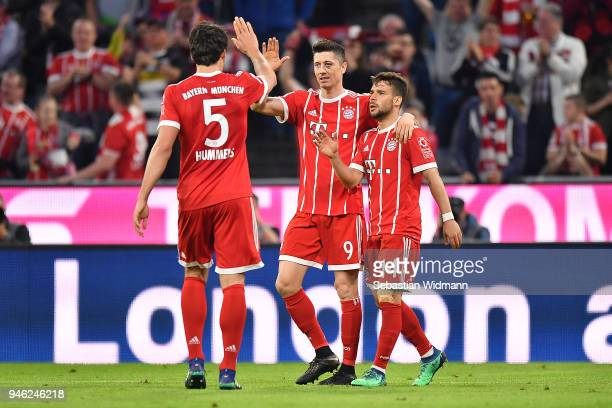 Robert Lewandowski of Bayern Muenchen celebrates with Juan Bernat of Bayern Muenchen and Mats Hummels of Bayern Muenchen after he scored a goal to...