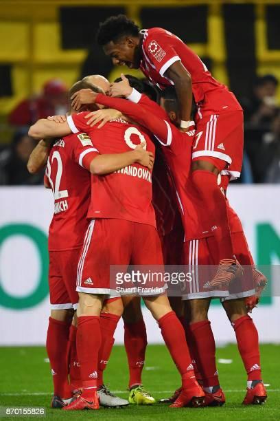 Robert Lewandowski of Bayern Muenchen celebrates with tea mates after he scored a goal to make it 02 during the Bundesliga match between Borussia...