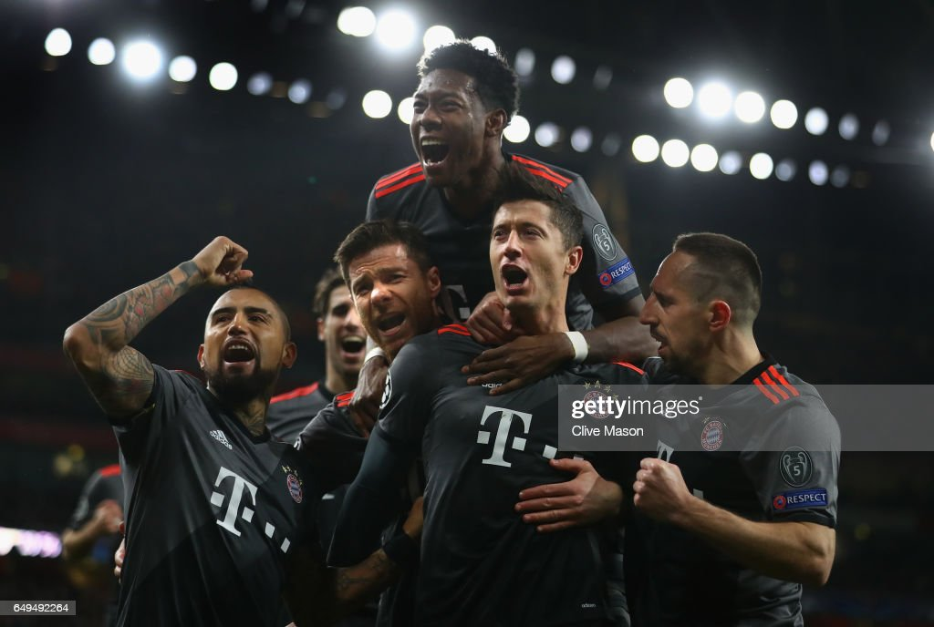 Robert Lewandowski of Bayern Muenchen (2R) celebrates with team mates as he scores their first goal from a penalty during the UEFA Champions League Round of 16 second leg match between Arsenal FC and FC Bayern Muenchen at Emirates Stadium on March 7, 2017 in London, United Kingdom.