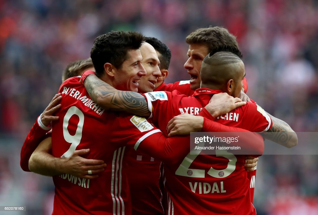 Robert Lewandowski of Bayern Muenchen celebrates with team mates after scoring his teams third goal during the Bundesliga match between Bayern Muenchen and Eintracht Frankfurt at Allianz Arena on March 11, 2017 in Munich, Germany.