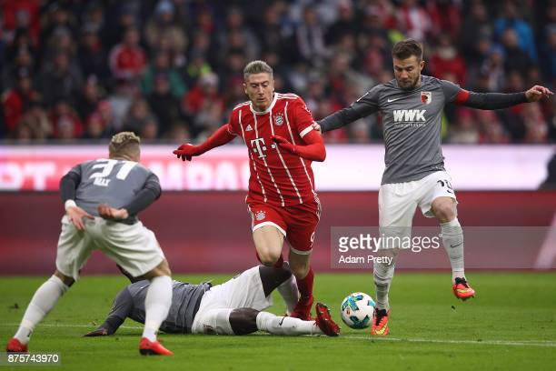 Robert Lewandowski of Bayern Muenchen fights for the ball with Kevin Danso of Augsburg during the Bundesliga match between FC Bayern Muenchen and FC...