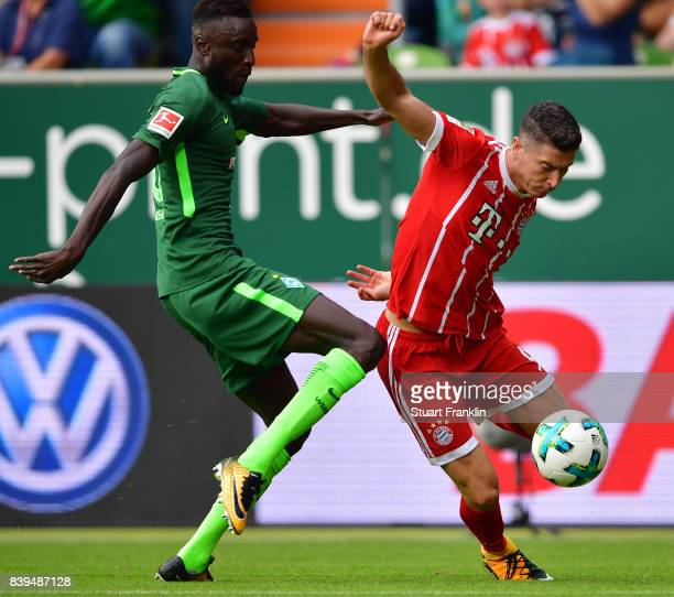 Robert Lewandowski of Bayern Muenchen fights for the ball with Lamine Sane of Bremen during the Bundesliga match between SV Werder Bremen and FC...