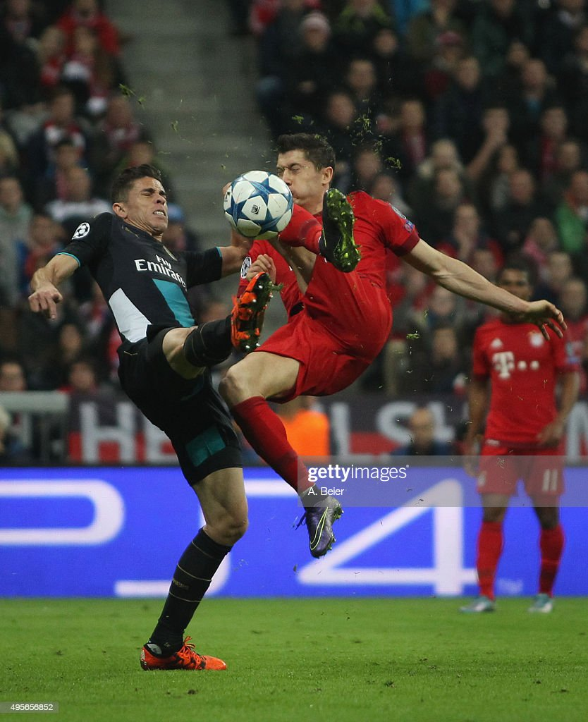 Robert Lewandowski (R) of Bayern Muenchen fights for the ball with Gabriel of Arsenal FC during the UEFA Champions League Group F match between Arsenal FC and FC Bayern Munchen on November 4, 2015 in Munich, Germany.