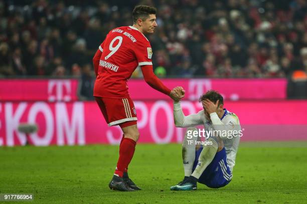 Robert Lewandowski of Bayern Muenchen helps Leon Goretzka of Schalke during the Bundesliga match between FC Bayern Muenchen and FC Schalke 04 at...