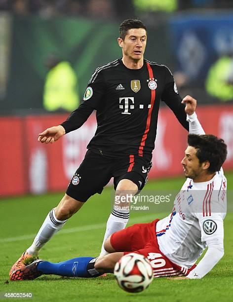 Robert Lewandowski of Bayern Muenchen is challenged by Gojko Kacar of Hamburger during the DFB Cup match between Hamburger SV and FC Bayern Muenchen...