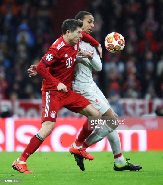 Robert Lewandowski of Bayern Muenchen is challenged by Joel Matip of Liverpool during the UEFA Champions League Round of 16 Second Leg match between...