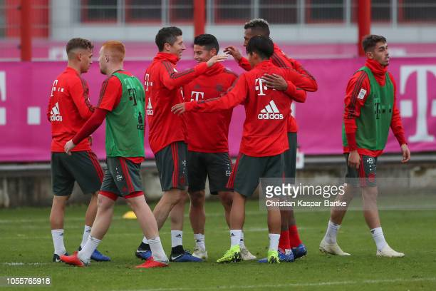 Robert Lewandowski of Bayern Muenchen James Rodriguez of Bayern Muenchen and Jerome Boateng of Bayern Muenchen have fun during a training session at...