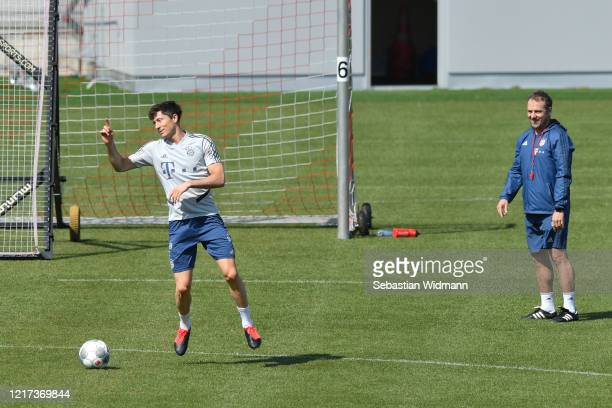 Robert Lewandowski of Bayern Muenchen jumps as head coach HansDieter Flick watches during a training session at Saebener Strasse training ground on...