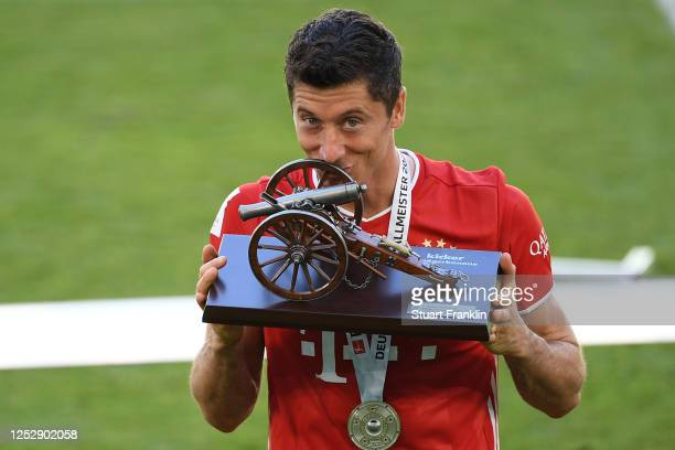 Robert Lewandowski of Bayern Muenchen kisses the trophy for the top goalscorer of the season after the Bundesliga match between VfL Wolfsburg and FC...