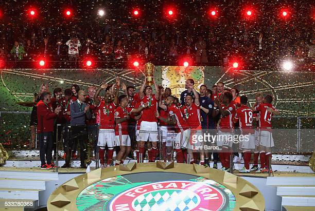 Robert Lewandowski of Bayern Muenchen lifts the trophy after winning the DFB Cup final match in a penalty shootout against Borussia Dortmund at...