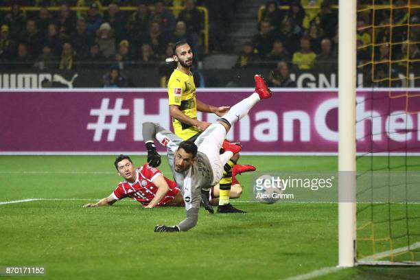 Robert Lewandowski of Bayern Muenchen Oemer Toprak of Dortmund and Roman Buerki of Dortmund look after the ball as Muenchen score their third goal to...