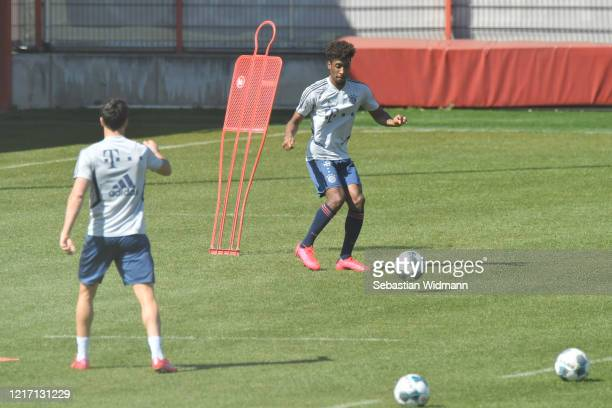 Robert Lewandowski of Bayern Muenchen passes the ball to Kingsley Coman during a training session at Saebener Strasse training ground on April 06...