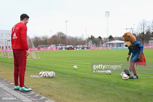 Robert Lewandowski of Bayern Muenchen plays with mascot Bernie dressed as Superman prior to a training session at Bayern Muenchen's training ground...
