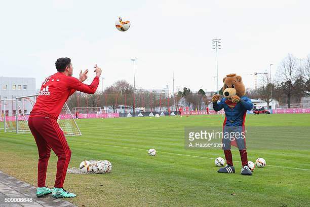 Robert Lewandowski of Bayern Muenchen plays with mascot Bernie dressed as Superman prior to a training session at Bayern Muenchen's training ground...