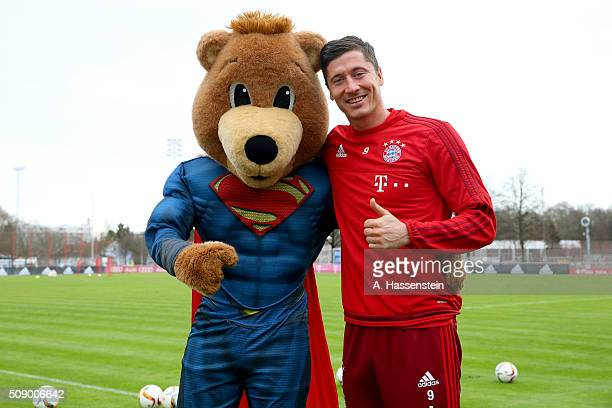 Robert Lewandowski of Bayern Muenchen poses with mascot Bernie dressed as Superman prior to a training session at Bayern Muenchen's training ground...