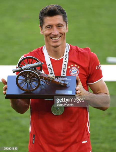 Robert Lewandowski of Bayern Muenchen poses with the trophy for the top goalscorer of the season after the Bundesliga match between VfL Wolfsburg and...