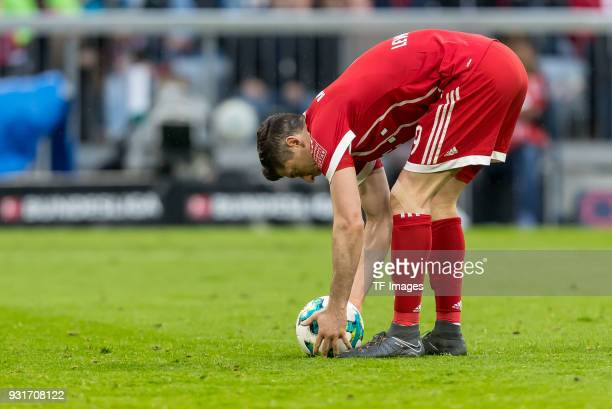 Robert Lewandowski of Bayern Muenchen prepares the ball to take a penalty kick during the Bundesliga match between FC Bayern Muenchen and Hamburger...
