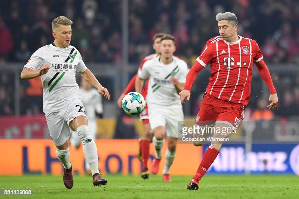 Robert Lewandowski of Bayern Muenchen runs with Matthias Ostrzolek of Hannover during the Bundesliga match between FC Bayern Muenchen and Hannover 96...