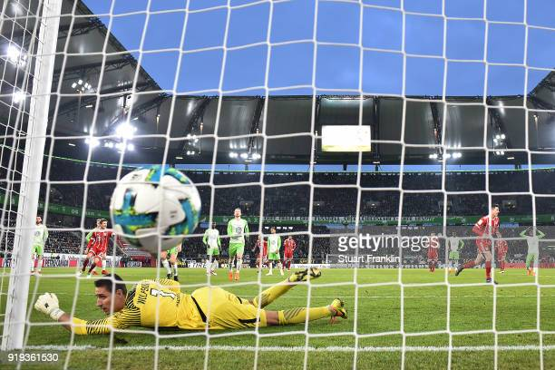 Robert Lewandowski of Bayern Muenchen scores a goal past goalkeeper Koen Casteels of Wolfsburg from the penalty spot to make it 12 during the...