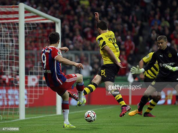 Robert Lewandowski of Bayern Muenchen scores his first goal against goalkeeper Mitchell Langerak and Sokratis of Dortmund during the DFB Cup semi...