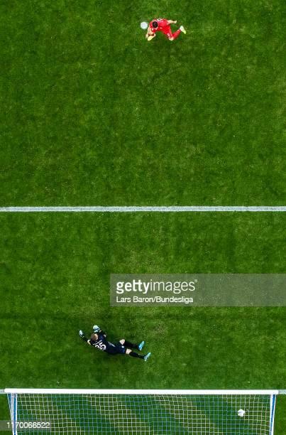Robert Lewandowski of Bayern Muenchen scores his teams first goal from the penalty spot against Alexander Nübel of Schalke during the Bundesliga...
