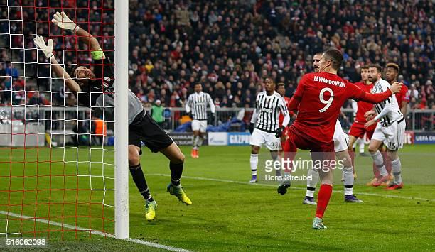 Robert Lewandowski of Bayern Muenchen scores his team's second goal against goalkeeper Gianluigi Buffon during the UEFA Champions League round of 16...