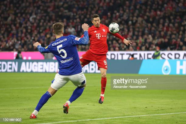 Robert Lewandowski of Bayern Muenchen scores the opening goal against Matija Nastasic of Schalke during the Bundesliga match between FC Bayern...