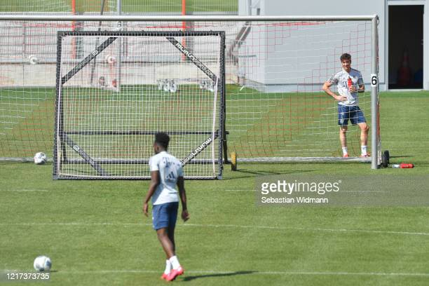 Robert Lewandowski of Bayern Muenchen watches his team mate Alphonso Davies during a training session at Saebener Strasse training ground on April 07...