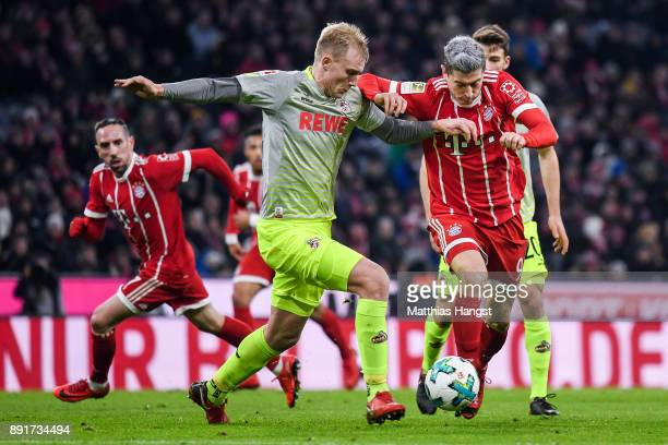 Robert Lewandowski of Bayern Munich and Frederik Sorensen of 1FC Koeln battle for the ball during the Bundesliga match between FC Bayern Muenchen and...