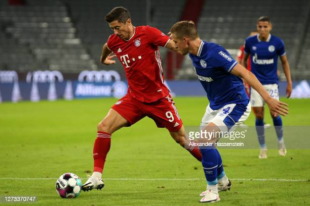 Robert Lewandowski of Bayern Munich battles for the ball with Bastian Oczipka of Schalke 04 during the Bundesliga match between FC Bayern Muenchen...