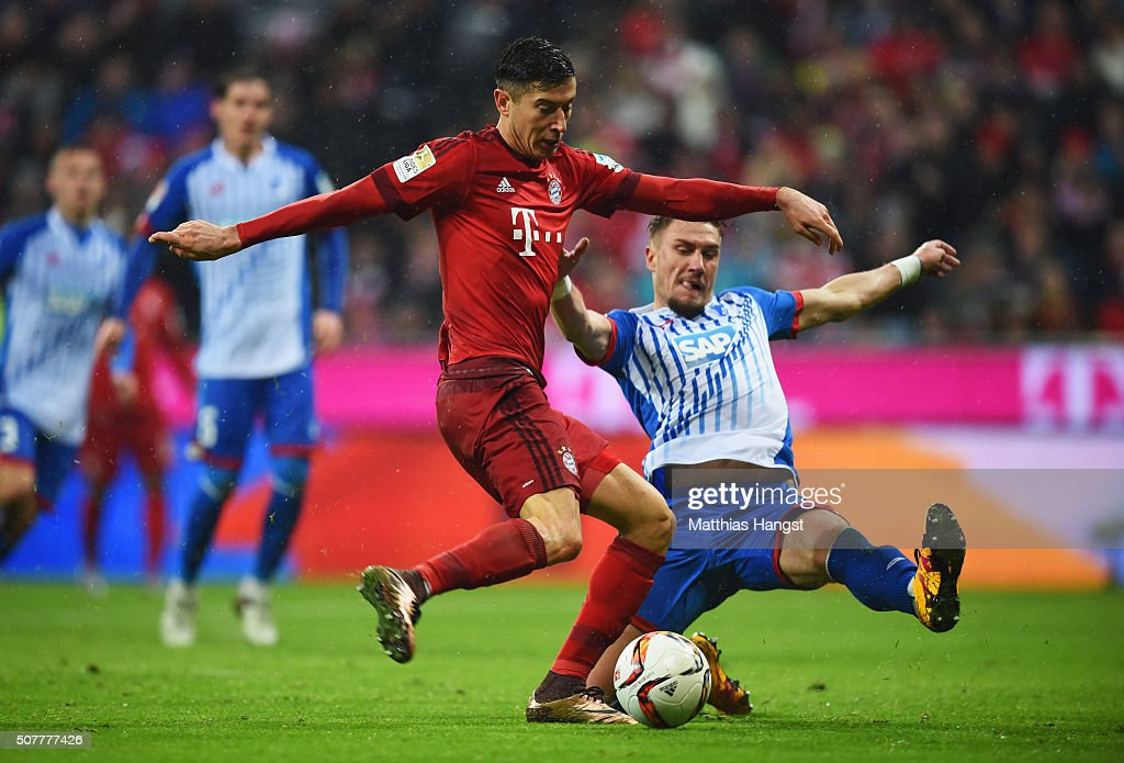 Robert Lewandowski of Bayern Munich beats Ermin Bicakcic of Hoffenheim to scores his and the team's second goal during the Bundesliga match between FC Bayern Muenchen and 1899 Hoffenheim at Allianz Arena on January 31, 2016 in Munich, Germany.