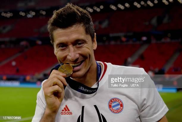 Robert Lewandowski of Bayern Munich bites into his UEFA Super Cup medal as he celebrates victory over FC Sevilla at Puskas Arena on September 24,...
