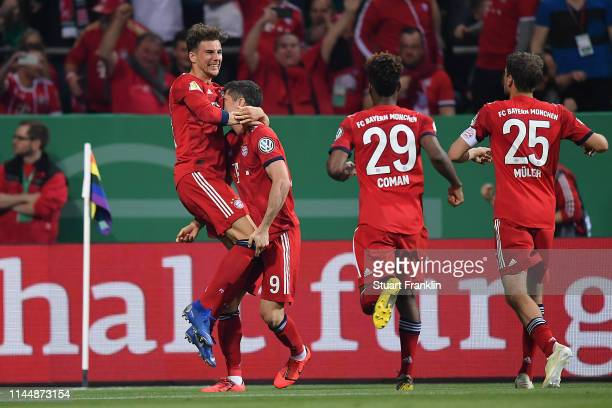 Robert Lewandowski of Bayern Munich celebrates after scoring his team's third goal from the penalty spot with his teammates during the DFB Cup semi...