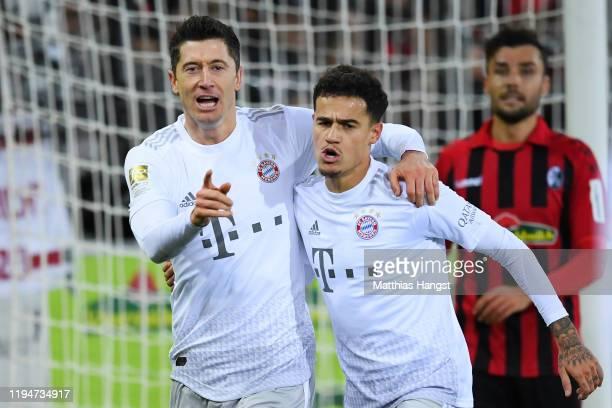 Robert Lewandowski of Bayern Munich celebrates scoring the opening goal with team-mate Philippe Coutinho during the Bundesliga match between...