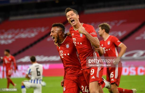 Robert Lewandowski of Bayern Munich celebrates with Corentin Tolisso after scoring his team's fourth goal from the penalty spot to complete his...