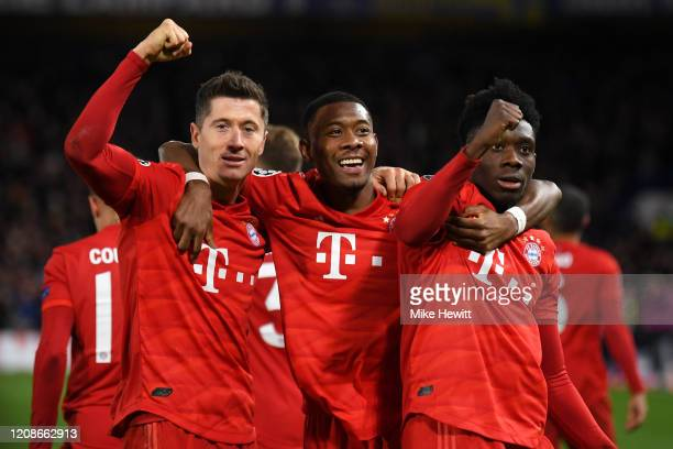 Robert Lewandowski of Bayern Munich celebrates with David Alaba and Alphonso Davies after he scores his team's third goal during the UEFA Champions...
