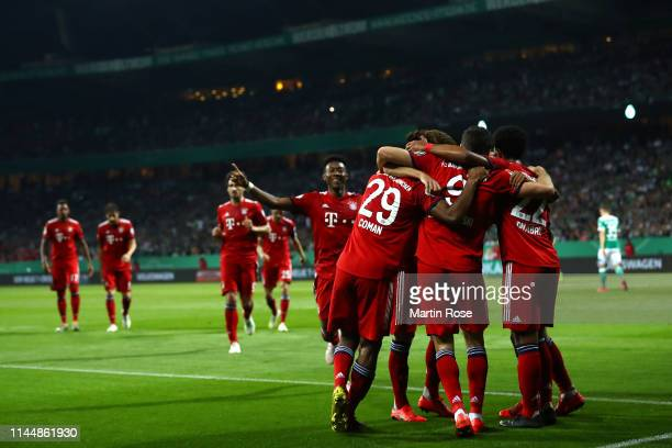 Robert Lewandowski of Bayern Munich celebrates with his teammates after scoring his team's first goal during the DFB Cup semi final match between...